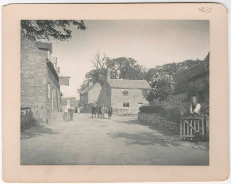 Black and white photograph showing a general  view with locals stood in village street near the Holly Bush Inn.