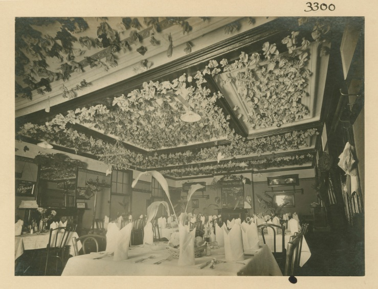 Interior view of an empty restaurant with serviettes full of pennies stuck to the ceiling.